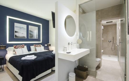 Fotografía del dormitorio y baño en suite de una vivienda de alquiler vacacional reformada